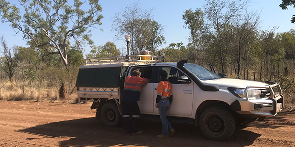 Two people standing next to a 4WD on a dirt road in the Australian bush.