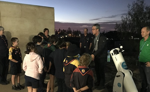Group of people outside at duck about to use a telescope.