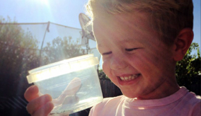 A smiling child with an insect in a container