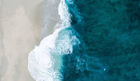 arial view of water lapping onto shore of white sand