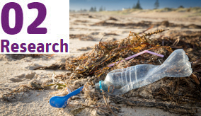 close up of plastic bottle and other rubbish on the beach