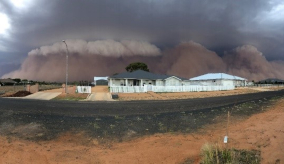 dust clouds rising up behind houses