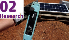 a hand holding a blue electronic device with a solar panel and red dirt in the background