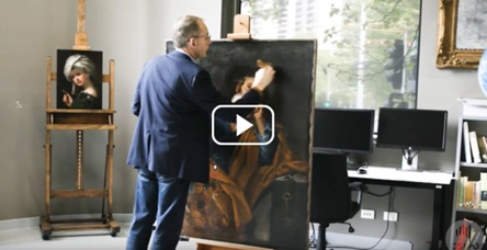 a man in a suit painting over an artwork in a studio