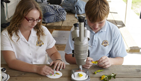 Two students with a microscope