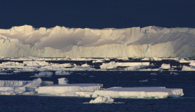 ice shelf and smaller ice bergs and a dark blue sky