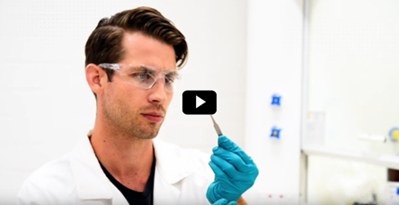 scientist in a lab coat and safety glasses looking at a sample with tweezers